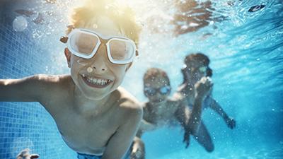 Barn simmar under vatten i pool