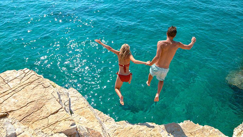 Par hoppar från klippa ner i havet i Kroatien