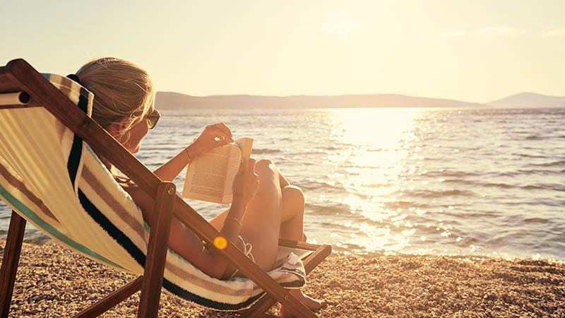 Kvinna läser bok i solstol på stranden i solnedgång