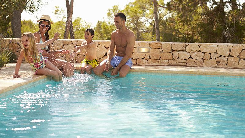 Familj leker vid poolen i Kroatien