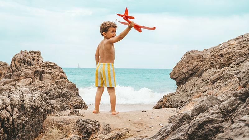 Barn står vid strand och håller leksaksflygplan