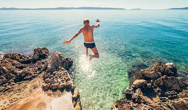 Man som hoppar ner i havet i Kroatien