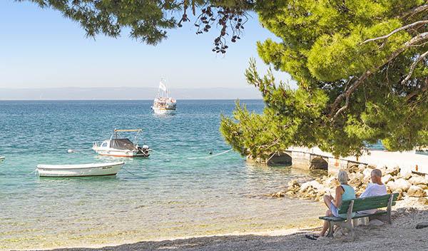 Par sitter vid stranden i Makarska, Kroatien